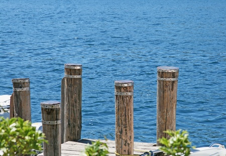Poles of a pier stainding over a blue lake photo