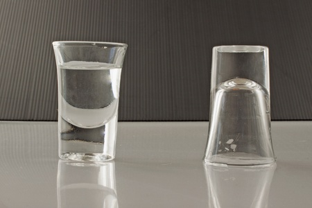 Two little glasses of transparent liquid, black in the background photo