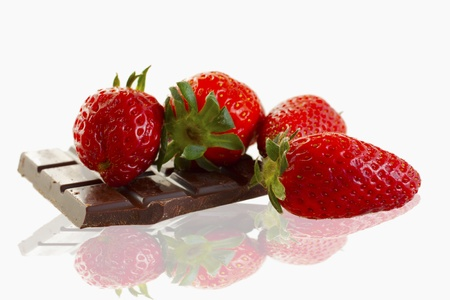 Four strawberries laying on a piece of chocolate, over white