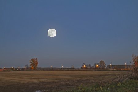 Big full moon over a landscape of empty fields photo