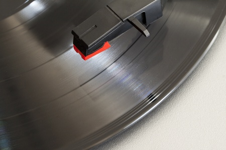 Closeup of needle over a wheeling record on a turntable photo