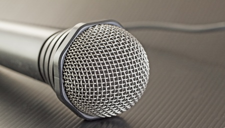 Gray microphone with wire over black background
