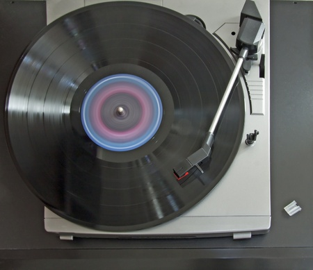 Closeup of spinning vinyl over a gray turntable