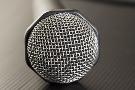 Gray microphone with wire over black background photo