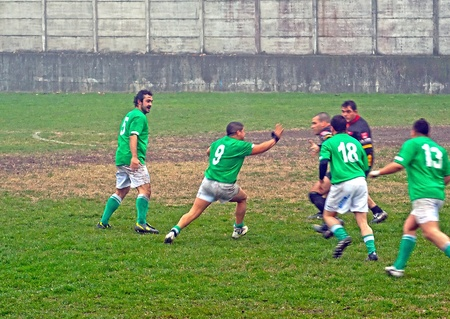 CASALE MONFERRATO, ITALY - NOVEMBER 20: Rugby game between Casale Le Tre Rose (green shirt) and Rugby La Spezia (black), Italian Serie C. Final result: Spezia 31-Casale 5. Casale player tries to avoid a tackle. November 20, 2011