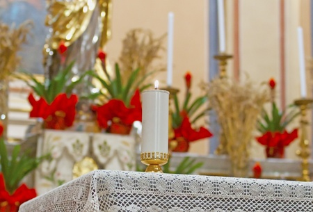 Candle lit on an altar with flowers on the back