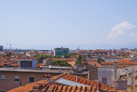 View of red old rooftops of a city under blue cloudy sky Stock Photo - 11764538