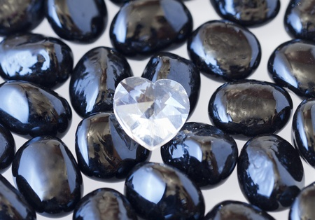 Little crystal heart between some black stones photo