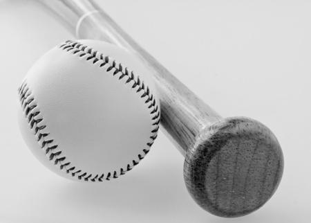 A baseball near a bat, balck and white image