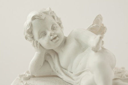 Detail of a little statue of smiling angel photo