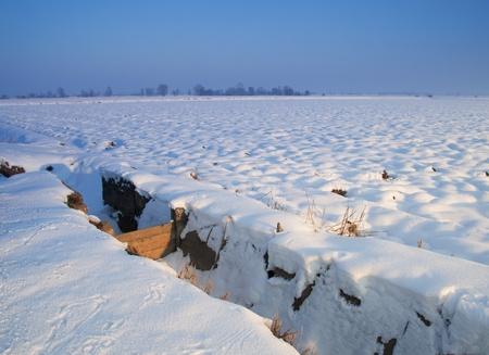 Fields canal under heavy snow, with blue sky photo