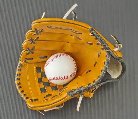 Baseball inside a leather glove over black photo