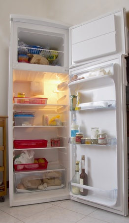 frig: An open white refrigerator with stuff within Stock Photo