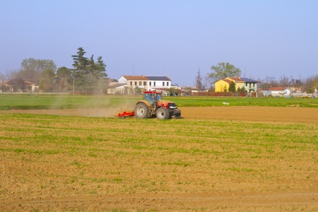 A red tractor working on a field photo