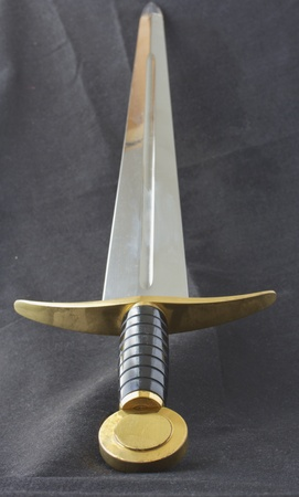 cross armed: Long medieval metal sword, with golden decoration on the hilt Stock Photo