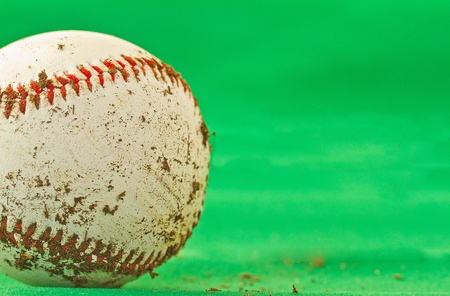 A dirty baseball over a green background photo