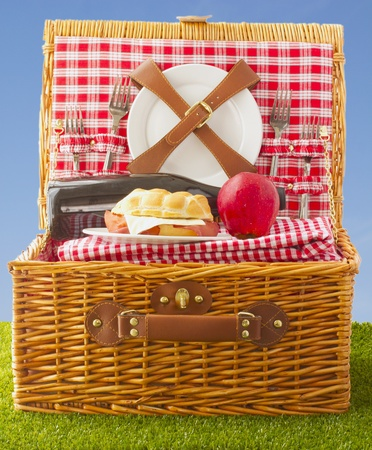 Wooden basket for picnic with sandwich, wine and apple over a grass field photo