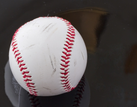 Rugged baseball over a black reflecting surface photo