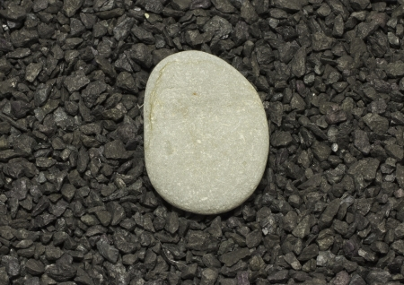 A gray stone over a background of little black stones Stock Photo - 14002437
