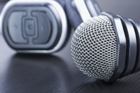 Gray microphone near a black headset, over black background photo