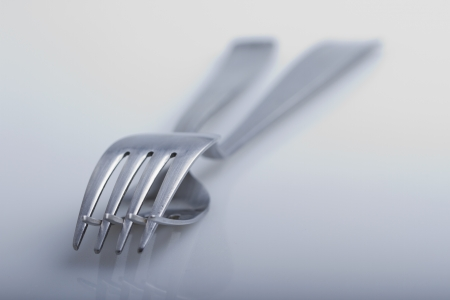 Two forks one over another overe white background photo