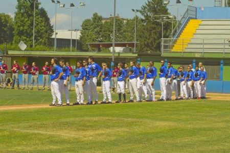 NOVARA, ITALY - JULY 7: Baseball game Novara (blue)-Bologna (purple) 1-17, Italian Serie A. Both teams standing on the field listening to national anthem. July 7, 2012
