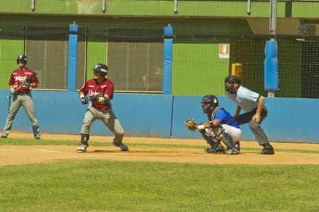 NOVARA, ITALY - JULY 7: Baseball game Novara (blue)-Bologna (purple) 1-17, Italian Serie A. Bologna shortstop Juan Carlos Infante tries a bunt. July 7, 2012