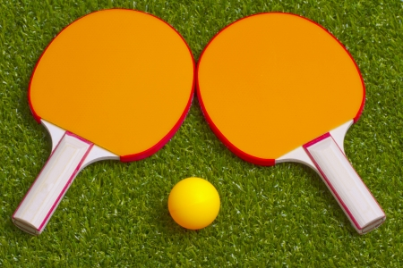 Two ping pong rackets with an orange ball photo