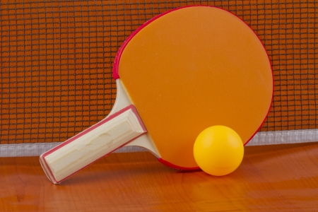table tennis orange racket with yellow ball near the net photo