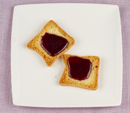 Two little toasts with rapsberry jam over white plate photo