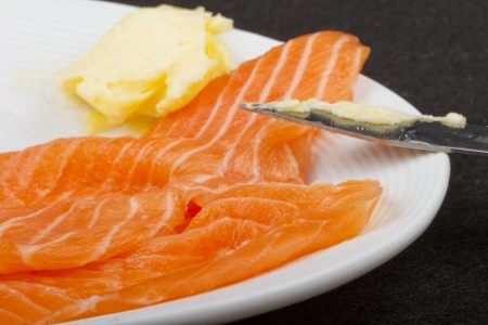A piece of salmon over a white plate, with butter