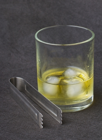 Whisky with ice over a black background, with an ice pick