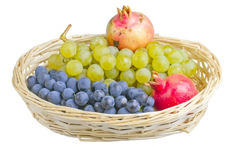 A basket with white and black grape and pomegranates