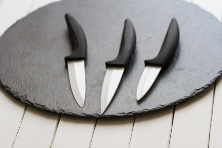 Three white ceramic blades over a black plate photo