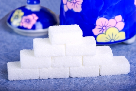 A pyramid made with cubes of sugar, with sugar bowl on the back photo