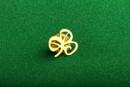 A golden clover over a green background photo