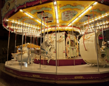 A Carousel running with lights at night Stock Photo