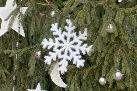 A Christmas decoration in form of snowflake over a green tree Stock Photo - 16985333