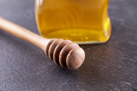 Close up of honey spoon over a black stone plate Stock Photo - 17038431