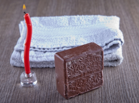 Brown soap, candle and towel over wooden background Stock Photo - 17090567