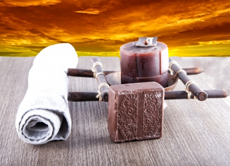 Brown soap, candle and towel over wooden background with sunset on the back Stock Photo - 17090569