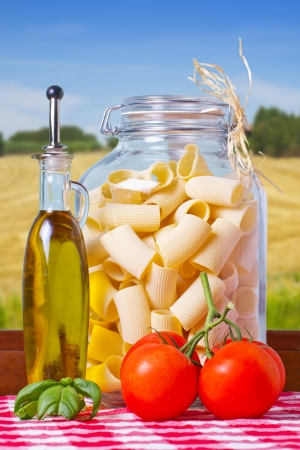 Typical Italian pasta inside a glass jar, with tomatoes and basil Stock Photo - 17090568