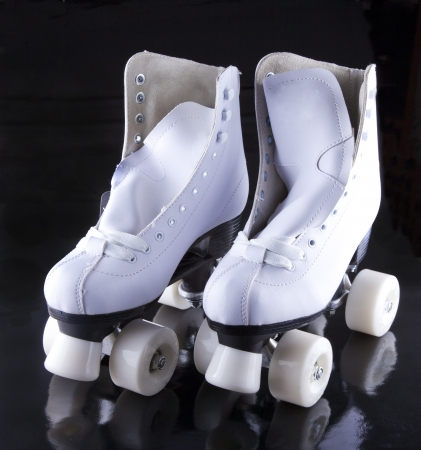 A pair of white roller skates over black background Stock Photo - 17415723