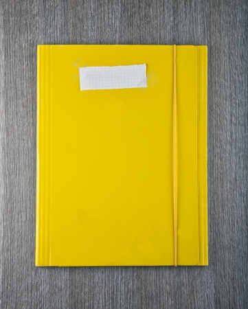 A yellow folder with empty white paper label photo