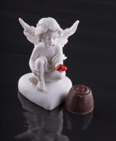 angel figurine: Close up of a little angel and a chocolate over black background Stock Photo