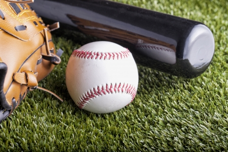 A baseball over green grass with bat and glove photo