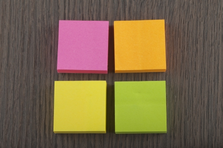 Four sticky notes of different colors over wooden background photo