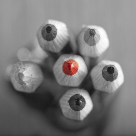 Red pencil in the middle of black and white bunch of pencils Stock Photo - 19656677