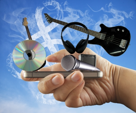 Male hand holding a smartphone, with music instruments and symbols photo