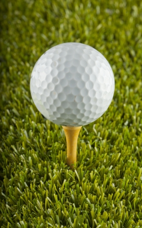 Close up of a white golf ball over a tee in the grass photo